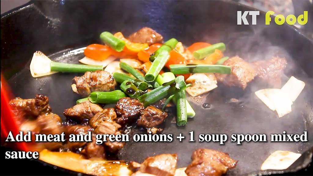 Shaking Beef stir frying and adding sauce and meat